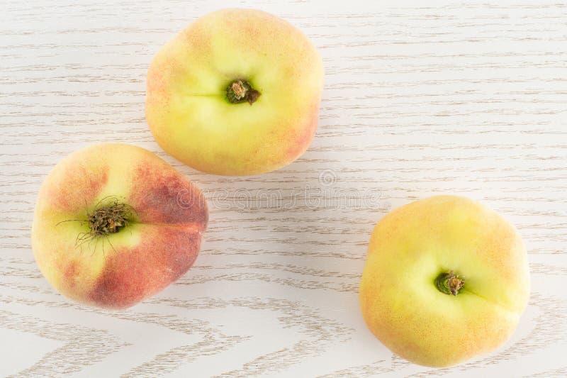 在灰色木头的新鲜的未加工的土星桃子 免版税库存照片
