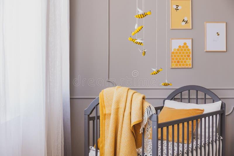 在灰色木小儿床的黄色毯子在明亮的婴孩卧室 免版税图库摄影