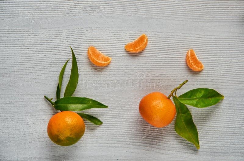 在灰色木板的三个蜜桔橙色切片有赠送阅本空间的 两与绿色叶子的新鲜的未加工的橘子 免版税库存照片