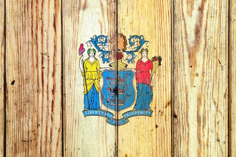 在灰色木板背景的新泽西美国各州国旗在蓝色红色不同颜色的独立的那天  免版税库存图片