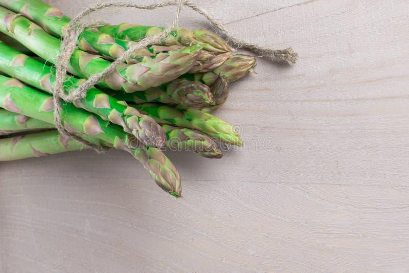 在灰色木背景的未加工的新绿色芦笋束与鞭子 库存图片