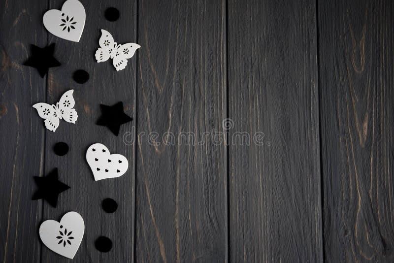 在灰色木背景的黑色和白色心脏星和蝴蝶 背景与星的青少年 超级明星 库存照片