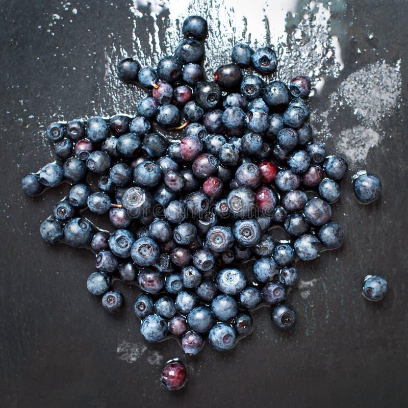 在灰色板岩石头的新近地被洗涤的有机蓝莓上 库存照片