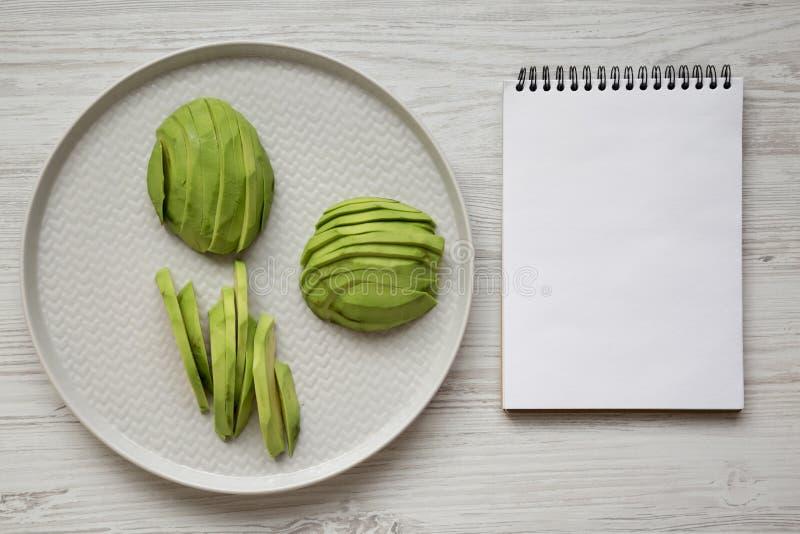 在灰色板材,在白色木桌,顶视图上的空白的笔记薄的切的鲕梨 顶上,从上面,平的位置 免版税库存照片
