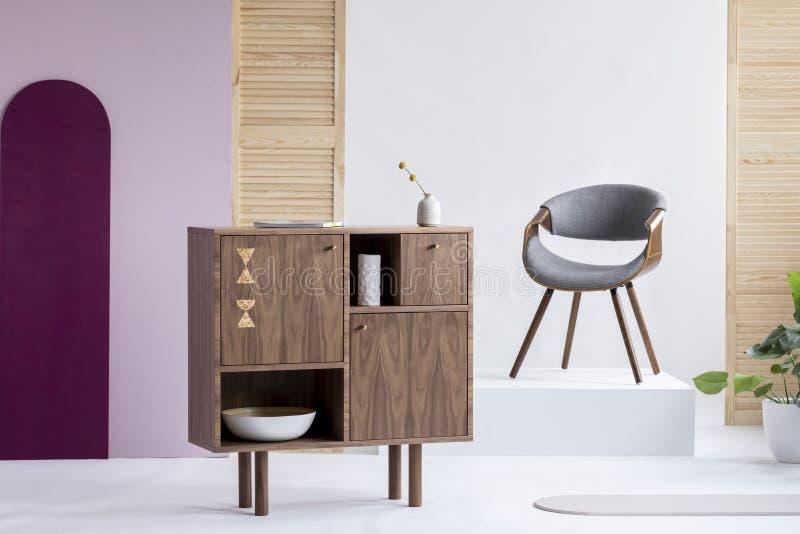 在灰色椅子旁边的时兴的木洗脸台在现代内部的白色平台 库存图片