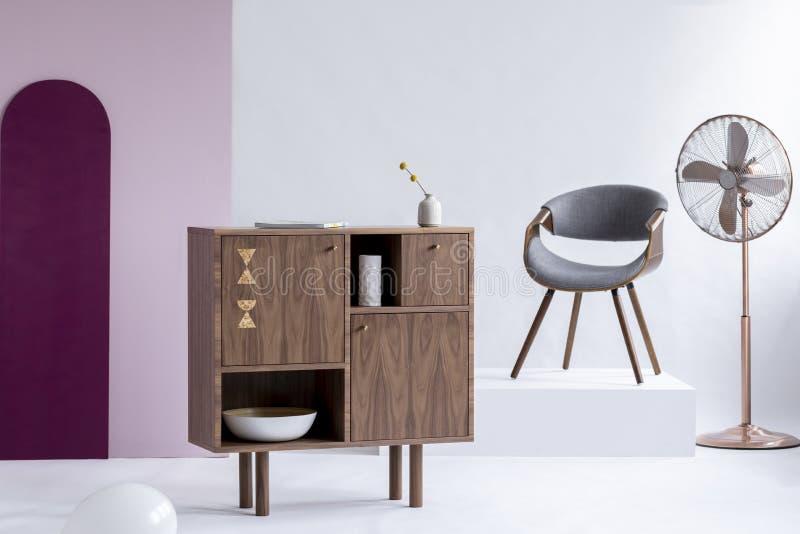 在灰色椅子旁边的时髦的木洗脸台在时髦内部的白色平台 免版税图库摄影