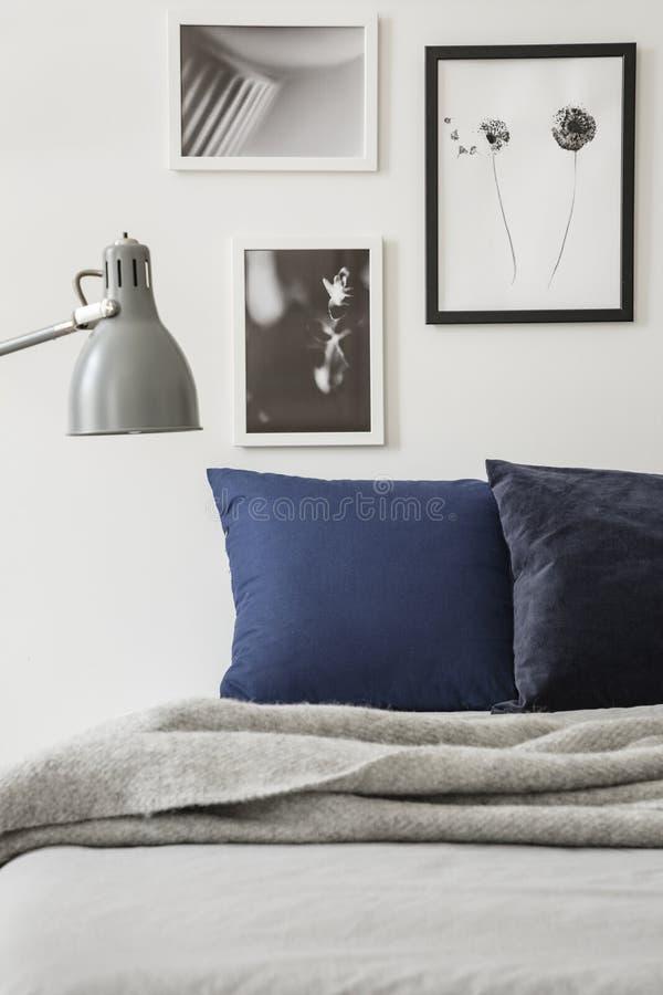 在灰色毯子上的灯在与坐垫的床在与海报的最小的卧室内部 实际照片 免版税库存照片