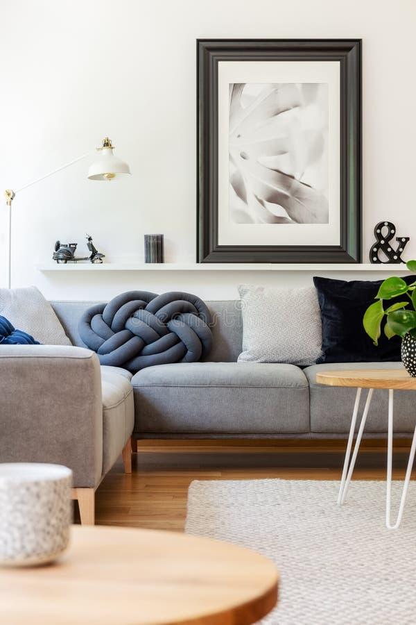 在灰色沙发上的海报有在白色客厅interi的坐垫的 库存照片