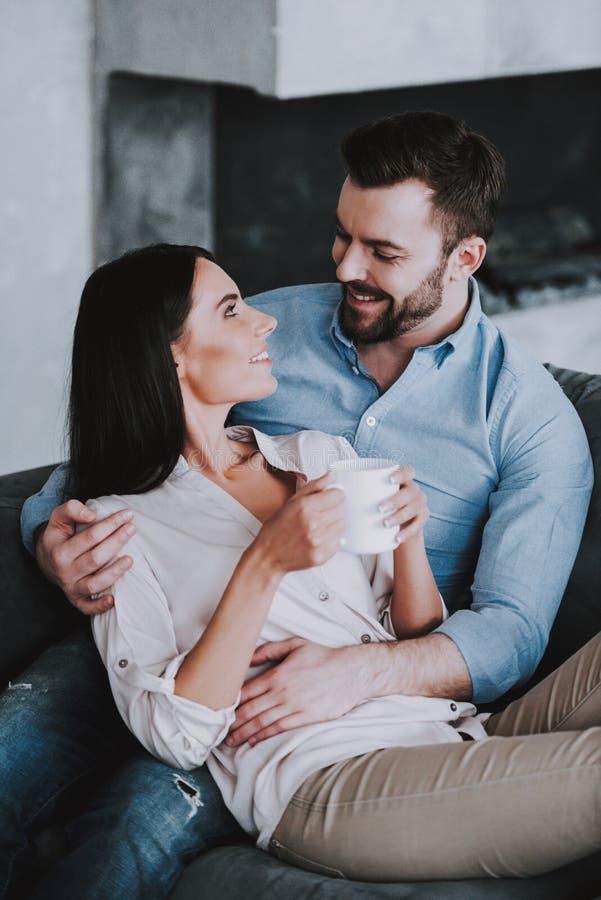在灰色沙发的年轻夫妇有枕头的在家 免版税库存照片