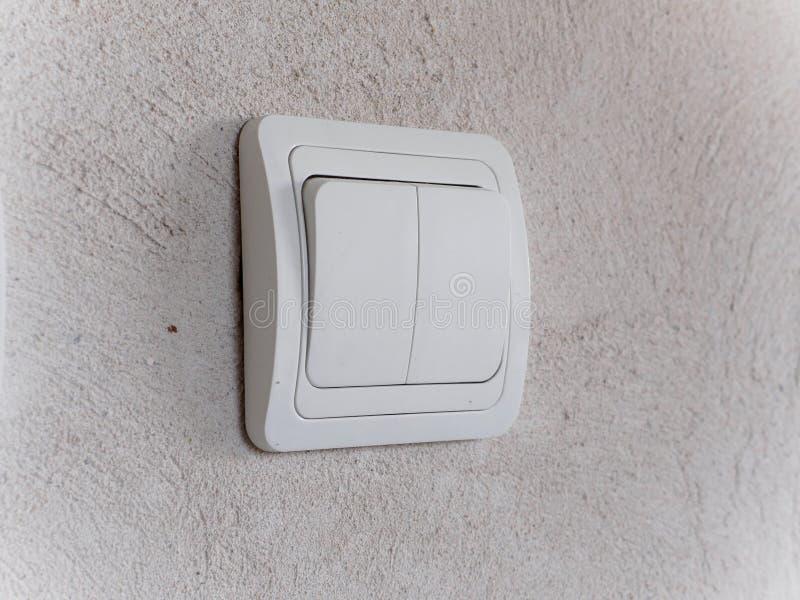在灰色混凝土墙上的现代白光开关 库存照片