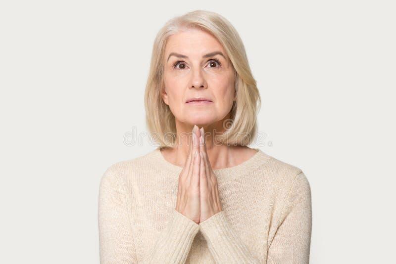 在灰色演播室背景隔绝的恳切年迈的妇女祈祷 免版税库存照片