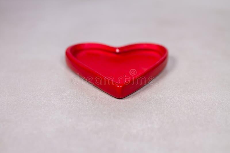 在灰色灰色大理石板岩背景的红色陶瓷心脏小雕象 库存图片