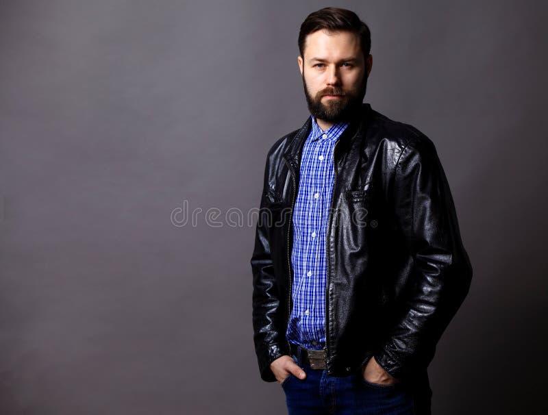 在灰色的有吸引力的年轻人佩带的皮夹克 免版税库存图片