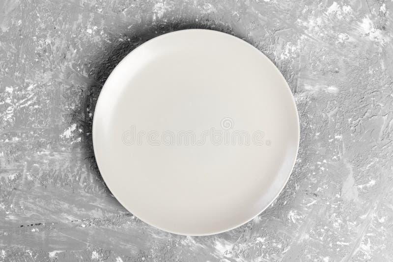 在灰色的背景的白色表面无光泽的圆的盘rextured桌 免版税图库摄影