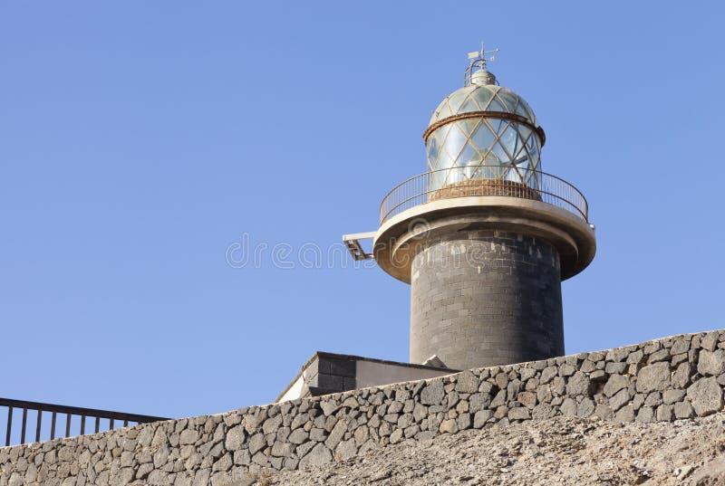 在灰色石墙, Jandia,加那利群岛上的玻璃顶面灯塔塔 免版税库存图片