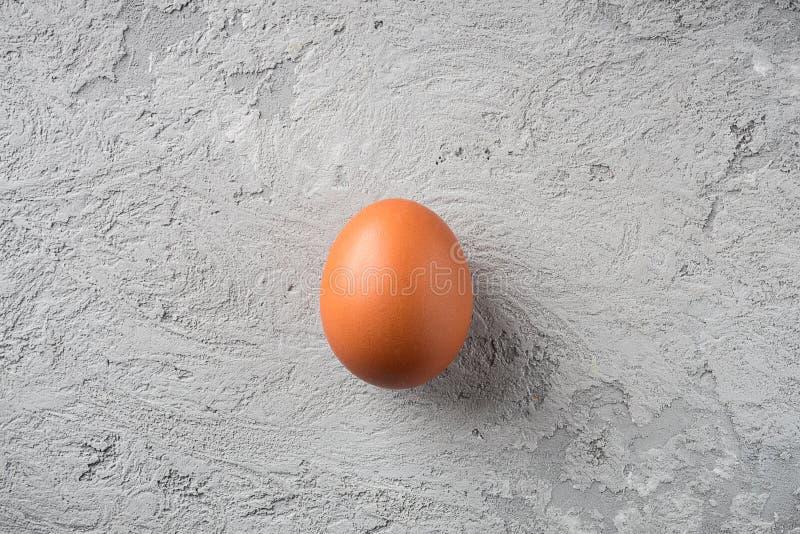 在灰色石背景概念食物的一个米黄鸡蛋是寂寞,比较是易碎和耐久的 免版税库存图片