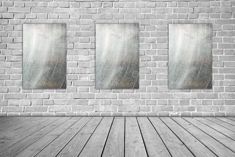 在灰色砖墙和木地板上的三种金属标志 库存照片