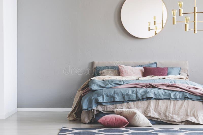 在灰色空的拷贝空间墙壁上的小鸡圆的镜子在典雅的卧室内部与与蓝色,粉红彩笔和米黄的温暖的床 免版税库存图片