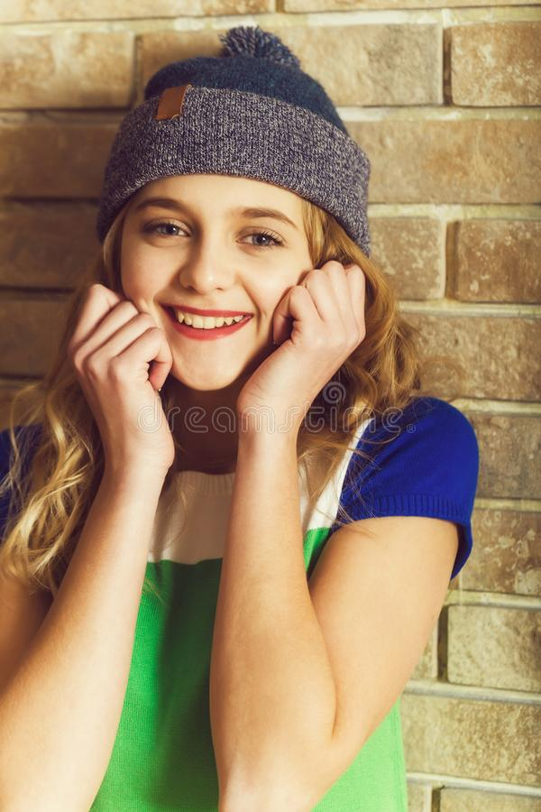 在灰色童帽帽子的愉快的俏丽的女孩微笑 免版税库存照片