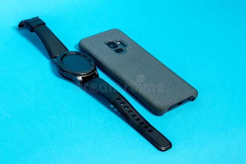 在灰色纺织品盒的智能手机和在蓝色背景的一块巧妙的手表 免版税库存照片