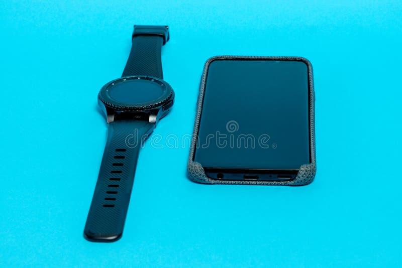 在灰色纺织品盒的智能手机和在蓝色背景的一块巧妙的手表 Clouse-up 图库摄影