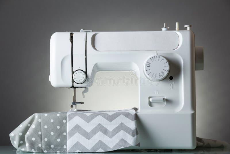 在灰色背景和织品裁减的白色现代电缝纫机 库存照片