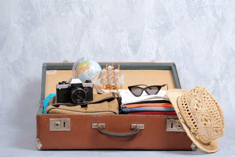 在灰色背景的充分的旅行手提箱,打开了与旅行衣物和辅助部件的案件 免版税图库摄影