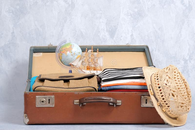 在灰色背景的充分的旅行手提箱,打开了与旅行衣物和辅助部件的案件 免版税库存图片