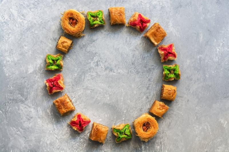 在灰色背景的各种各样的中东甜点 构筑阿拉伯甜点圈子,果仁蜜酥饼,曲奇饼 顶视图,平的位置,拷贝 图库摄影