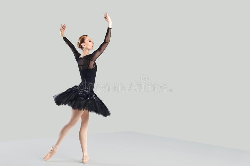 在灰色背景的妇女跳芭蕾舞者 免版税库存图片