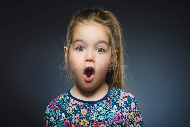 在灰色背景的小女孩去的惊奇特写镜头画象  免版税库存图片