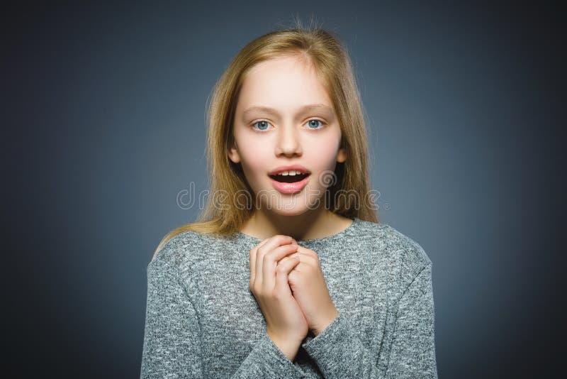 在灰色背景的小女孩去的惊奇特写镜头画象  免版税库存照片