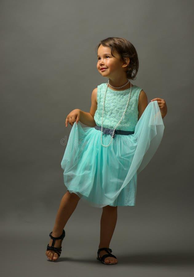 在灰色背景的小的逗人喜爱的女孩跳舞 库存图片