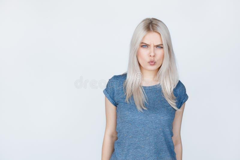 在灰色背景的恼怒的少年女孩 免版税图库摄影