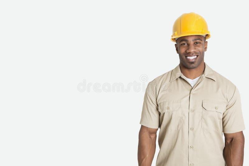 头戴在灰色背景的愉快的年轻非洲人画象黄色安全帽盔甲 库存照片