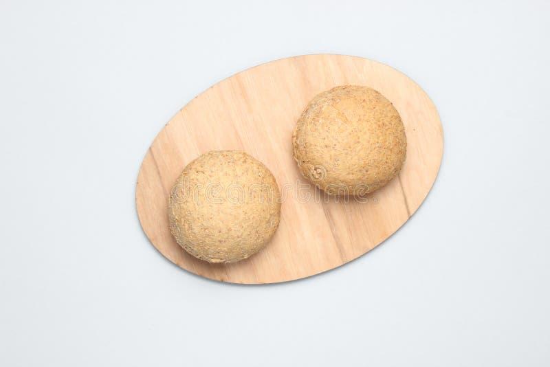 在灰色背景的整个五谷小圆面包 库存照片
