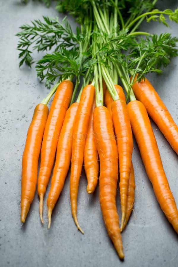 在灰色背景的新鲜的红萝卜 图库摄影