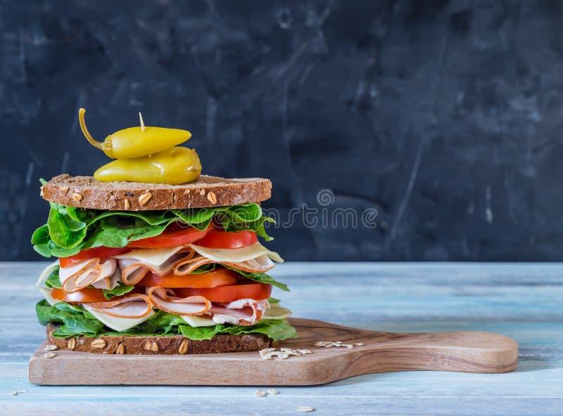 在灰色背景的最后熟食店三明治 库存图片