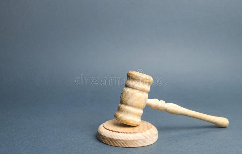 在灰色背景的法官的锤子 司法系统 准则、规则和法律 解决冲突法庭上 法案 库存照片