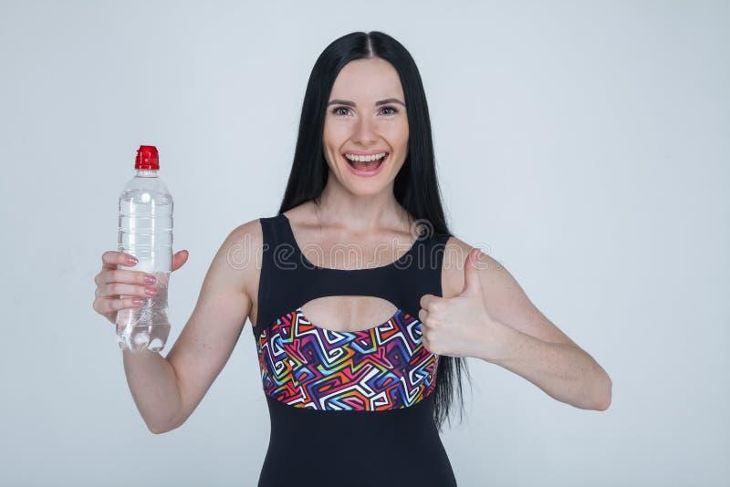 在灰色背景的美丽的微小的深色的少女体育衣裳 拿着一个瓶水和展示的运动的健康模型 免版税库存照片