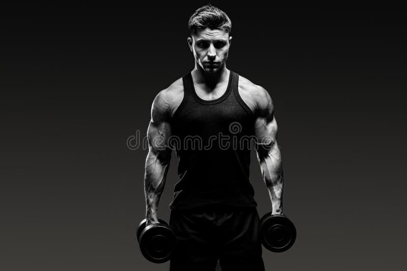 在灰色背景的肌肉爱好健美者人黑白照片 库存照片