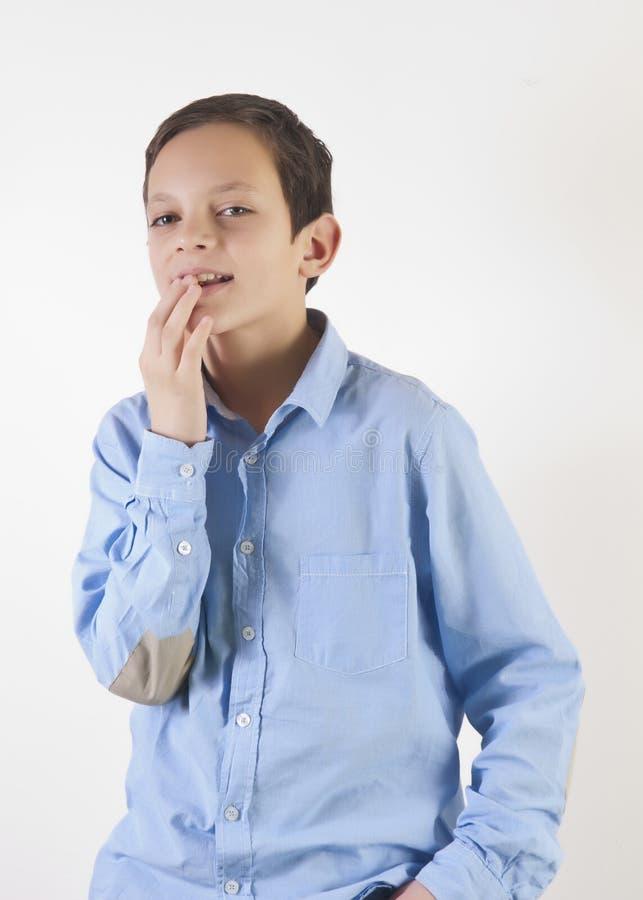 在灰色背景的青春期前的男孩画象 图库摄影