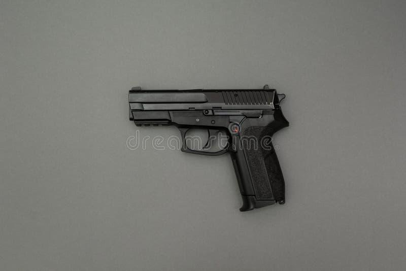 在灰色背景的黑枪 库存照片