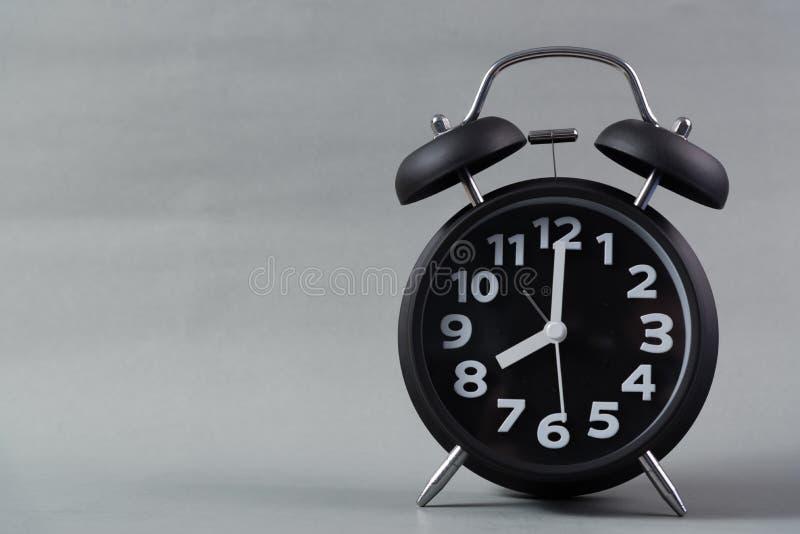 在灰色背景的黑颜色葡萄酒闹钟,叫醒时间 库存照片