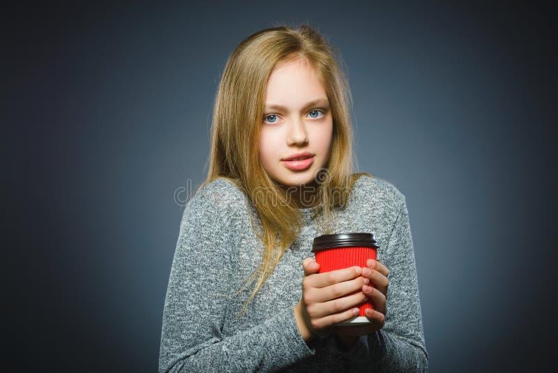 在灰色背景隔绝的十几岁的女孩饮料红色咖啡 库存照片