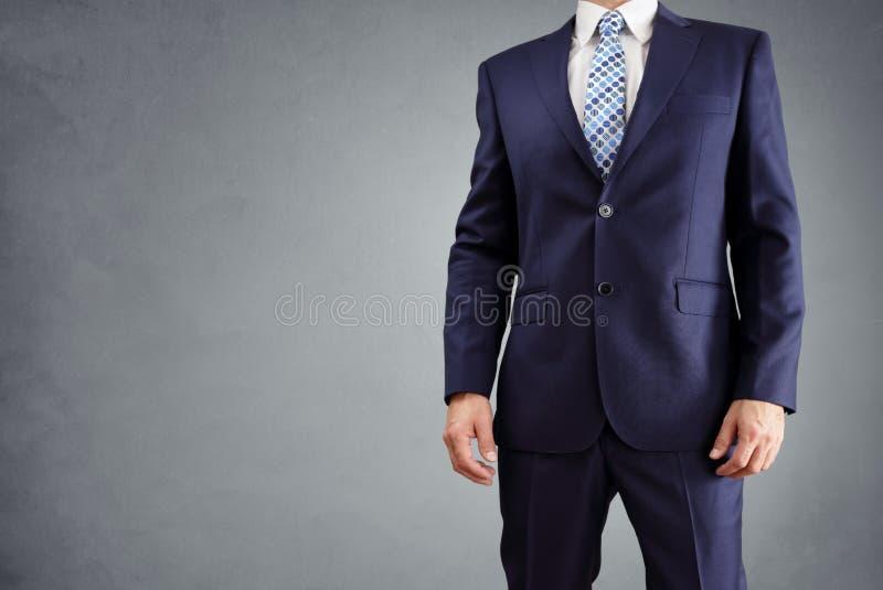 在灰色背景隔绝的衣服的商人 免版税库存照片