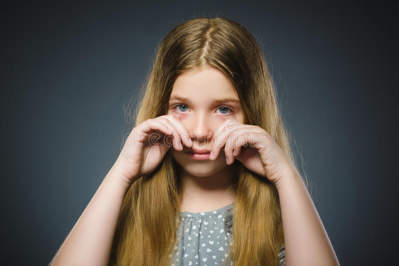 在灰色背景隔绝的进攻哭泣的女孩 免版税库存照片