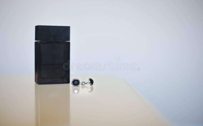 在灰色背景隔绝的黑香水瓶和银链扣 婚礼辅助部件 免版税库存照片
