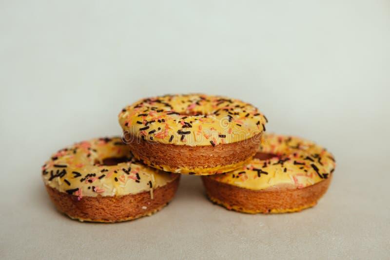 在灰色背景,美丽的甜食物的三个黄色油炸圈饼饼干 免版税库存照片