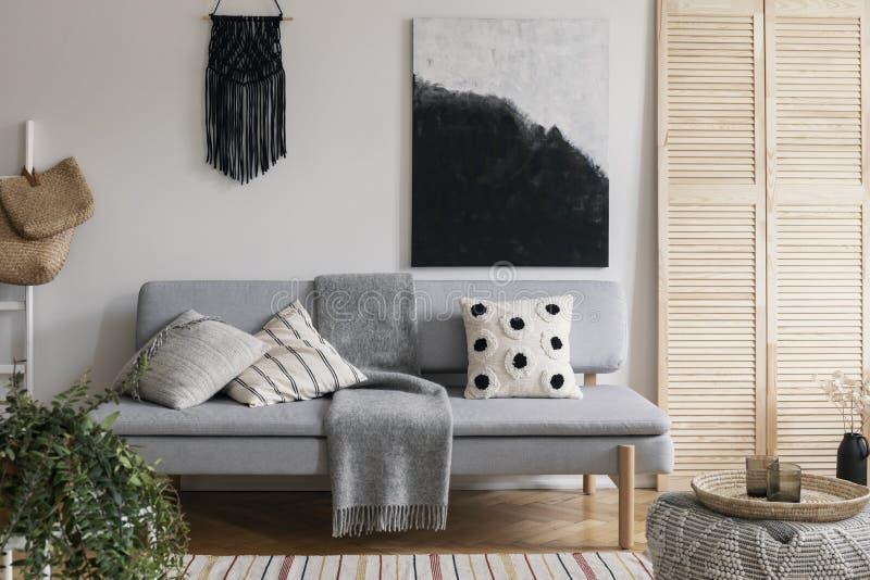 在灰色舒适的长沙发上的黑手工制造花边有枕头和温暖的毯子的,与大模型的真正的照片在空的墙壁上 免版税库存图片